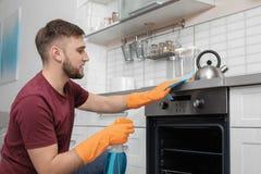 Mensen schoonmakende oven met vod en detergens in keuken stock afbeelding