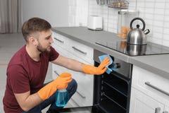 Mensen schoonmakende oven met vod en detergens in keuken stock fotografie