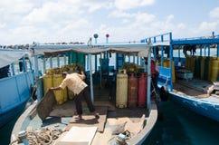 Mensen schoonmakende vloer in boot bij dokkengebied Stock Afbeelding