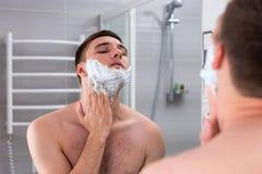 Mensen smerend schuim voor scheerbeurt op zijn gezicht in de badkamers Stock Fotografie