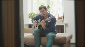 Mensen speelmuziek door houten akoestische gitaar Mens die Akoestische Gitaar dicht omhoog langzame geanimeerde video spelen in d stock footage