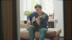 Mensen speelmuziek door houten akoestische gitaar Mens die Akoestische Gitaar dicht omhoog langzame geanimeerde video spelen in d stock video