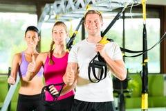 Mensen in sportgymnastiek op opschortingstrainer Stock Foto's