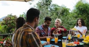 Mensen spreken die voedsel overgaan die op terras jonge vrienden eten die bij lijst in openlucht mededeling zitten stock video