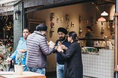 Mensen status, die voedsel eten bij Stadsmarkt wordt gekocht, Londen, het UK Stock Afbeelding