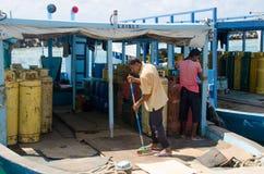 Mensen swepts vloer in boot bij dokkengebied Stock Fotografie