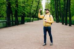 Mensen, technologie, levensstijl en ontspanningsconcept Knappe mens die geel jasje, zwart GLB en jeans dragen die zich in parkdri royalty-vrije stock foto