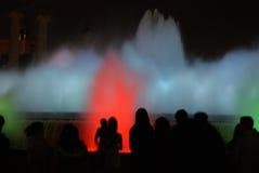 Mensen tegen de kleurrijke fontein stock afbeeldingen
