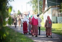 Mensen in traditionele Russische klerengang tussen blokhuizen stock fotografie