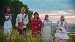 Mensen in traditionele volkskleren die op het gebied lopen en een lied zingen - zonsondergang stock videobeelden