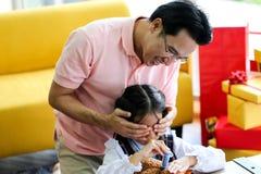 Mensen verbergende gift voor Ouder en weinig kind die pret hebben dichtbij Chri royalty-vrije stock fotografie