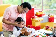 Mensen verbergende gift voor Ouder en weinig kind die pret hebben dichtbij Chri stock afbeeldingen