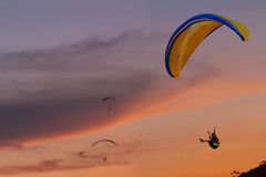 Mensen vliegend glijscherm bij zonsondergang met oranje achtergrond Stock Foto