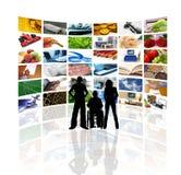 Mensen voor muur van de TVschermen Stock Afbeelding