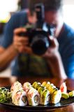Mensen, vrije tijd, voedsel, voedsel en technologie - sluit omhoog van de mens met camera die een beeld van sushi in het restaura stock afbeelding