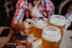 Mensen, mensen, vrije tijd, vriendschaps en vieringsconcept - gelukkige mannelijke vrienden die bier drinken en glazen clinking b Royalty-vrije Stock Foto's