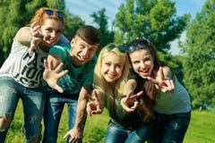 Mensen, vrijheid, geluk, en tienerconcept - de groep gelukkige vrienden gaat en pret op een achtergrond van groene bomen uit Stock Foto's