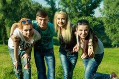 Mensen, vrijheid, geluk, en tienerconcept - de groep gelukkige vrienden gaat en pret op een achtergrond van groene bomen uit Stock Afbeeldingen