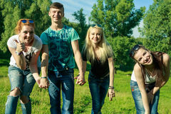 Mensen, vrijheid, geluk, en tienerconcept - de groep gelukkige vrienden gaat en pret op een achtergrond van groene bomen uit Royalty-vrije Stock Afbeelding
