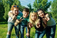 Mensen, vrijheid, geluk, en tienerconcept - de groep gelukkige vrienden gaat en pret op een achtergrond van groene bomen uit Stock Afbeelding