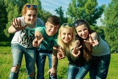 Mensen, vrijheid, geluk, en tienerconcept - de groep gelukkige vrienden gaat en pret op een achtergrond van groene bomen uit Stock Fotografie