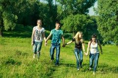 Mensen, vrijheid, geluk, en tienerconcept - de groep gelukkige vrienden gaat en pret op een achtergrond van groene bomen uit Royalty-vrije Stock Foto