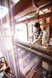 Mensen wevend tapijt op traditioneel houten weefgetouw stock afbeelding