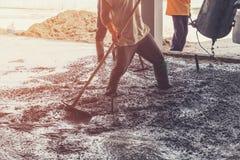 Mensenarbeiders die vers gegoten concrete mengeling bij de bouw uitspreiden Royalty-vrije Stock Foto's