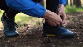 Mensenband het kant tijdens looppas op bosweg De close-upblik van bemant handen die het kant in bos binden stock videobeelden
