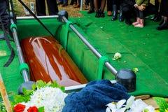 Mensenbegrafenis die de doodskist neerzetten bij een begrafenis stock foto's