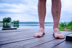 Mensenbenen die zich op een dok bevinden terwijl het ontspannen op kust Stock Afbeeldingen