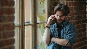Mensenbesprekingen op telefoon door venster stock videobeelden