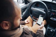 Mensenbestuurder die mobiele telefoon met gps toepassing in zijn auto, moderne navigatietechnologie voor reis houden en concept d stock fotografie