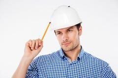 mensenbouwer in de bouw van helm met potlood het denken Royalty-vrije Stock Fotografie
