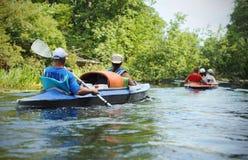 Mensencanoeing in een kleine rivier in de zomer stock afbeelding