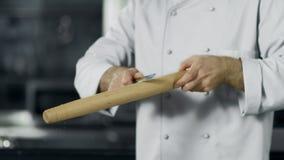Mensenchef-kok die rol schoonmaken op het werk De handen die van de close-upmens voorbereidingen treffen te koken stock footage