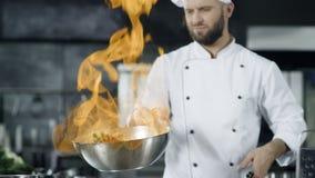 Mensenchef-kok het koken in pan met brand in langzame motie bij keuken Jonge chef-kok stock footage