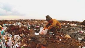Mensendaklozen in stortplaatsdaklozen die voedsel onder het huisvuil zoeken de sociale honger van de de armoedearmoede van het co stock videobeelden