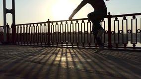 Mensendansen Jive op een Moderne Brug in de Stralen van Schitterende Zonsondergang in slo-Mo stock video