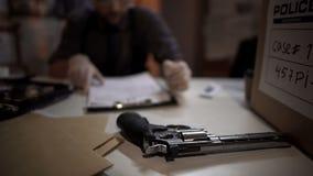 Mensendetective het inspecteren revolverkanon en het vullende onderzoek van het deskundigheidsrapport royalty-vrije stock foto's