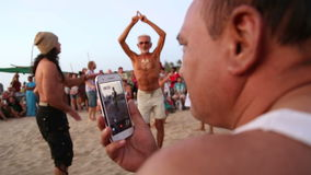 Mensenfilm op mobiele telefoonmensen die op het strand dansen stock video