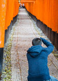 Mensenfotograaf die beelden in het Heiligdom van fushimiinari nemen Stock Afbeeldingen