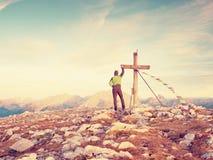 Mensengang langs het houten die kruis bij een bergpiek aan Alpen wordt gebouwd victiims Kruis op Bovenkant Royalty-vrije Stock Afbeeldingen