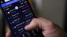 Mensengebruik een smartphone voor Internet-handelcrypto munt Langzame Motie stock footage
