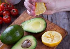 Mensenhand die citroen op avocado drukken stock foto's