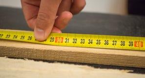 Mensenhand die een houten plank met gele maatregelenband meten royalty-vrije stock fotografie
