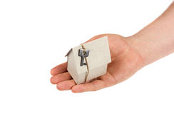 Mensenhand die een model van kartonhuis houden die met sleutel op streng op witte achtergrond wordt geïsoleerd Stock Foto