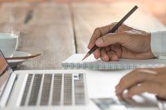 Mensenhand die een nota schrijven en op laptop klikken Royalty-vrije Stock Foto
