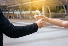 Mensenhand die fles drinkwater na het runnen van oefening bij de straat geven stock afbeelding