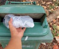 Mensenhand die leeg plastic glas water werpen in een groene bak voor de conceptenbest practice voor milieubesparing royalty-vrije stock foto's